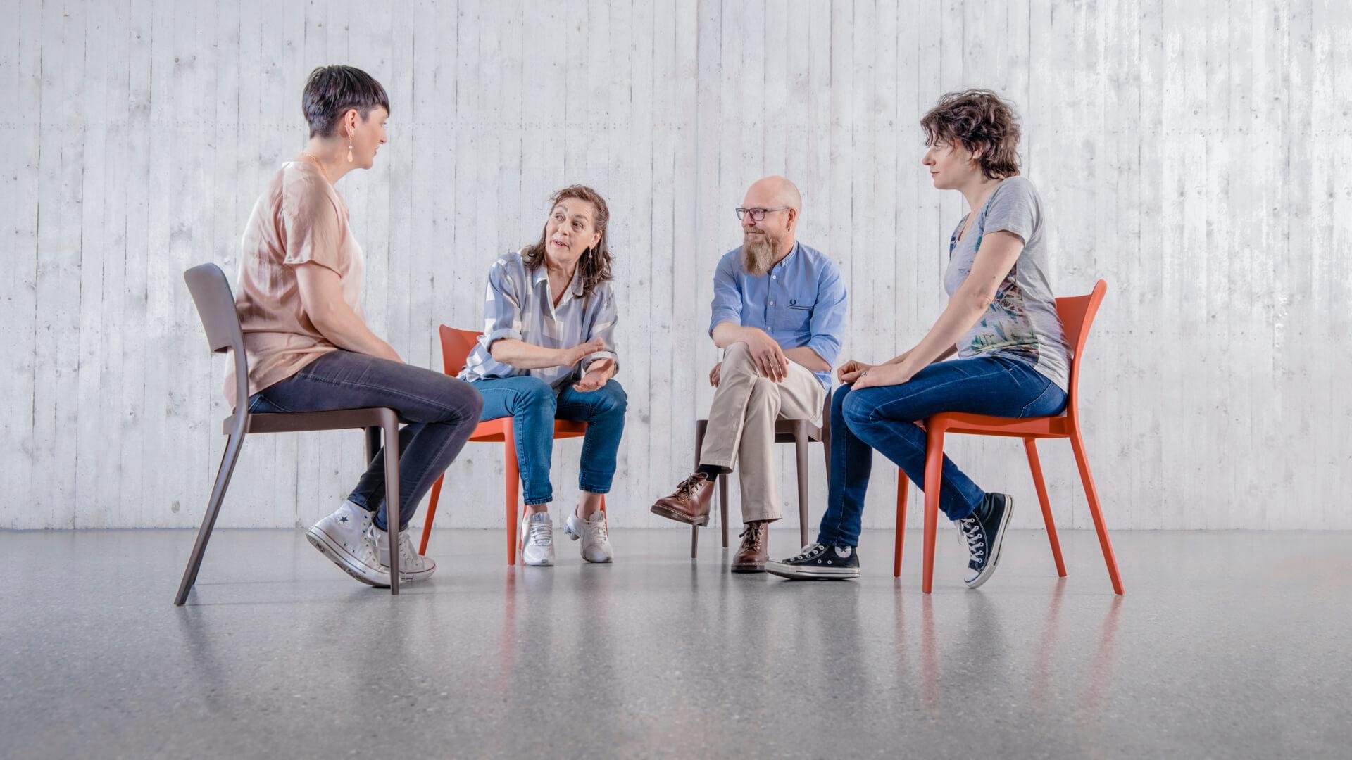 Drei Frauen und ein Mann sitzen in einer Runde und unterhalten sich