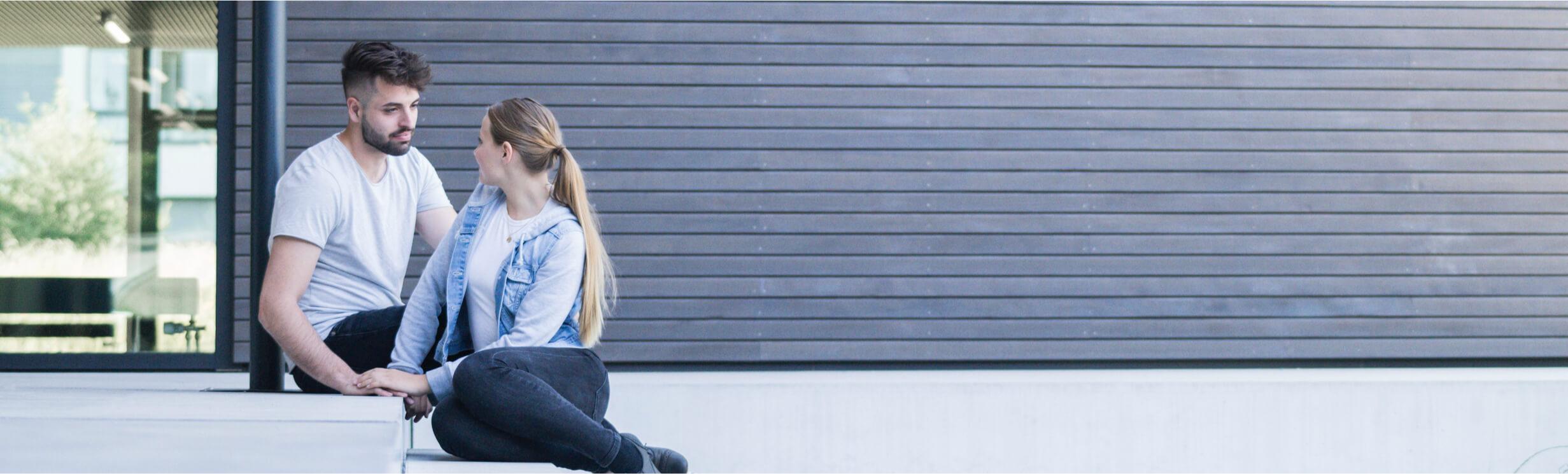 ein junges paar sitzt auf einer treppe und schaut sich an