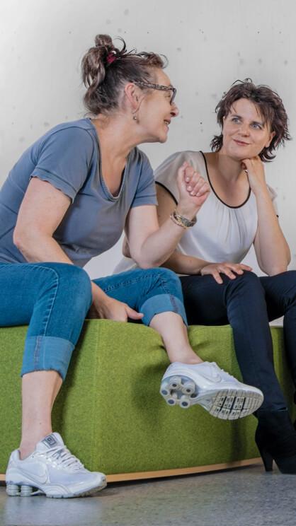 Zwei Frauen sitzen nebeneinander und unterhalten sich