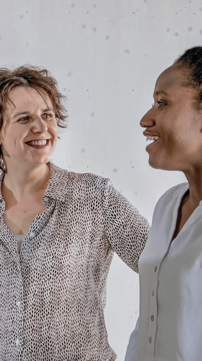 Zwei Frauen stehen nebeneinander und unterhalten sich